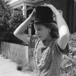 "Title: ""Top Hat"" Image of Jane Corkin. Recorded Queen Street, Toronto ON Canada. There was a top hat on the back seat of my car. Jane removed it to try on for size."